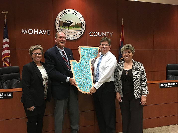 The board accepted donated artwork of turquoise tiles laid onto a copper plate in the shape of Mohave County, recognizing contributions from Origin Mining Co. for the copper; Kingman Turquoise Mining Co. and Colbaugh Processing for the turquoise; artist Gregg Arnold and Antares Art Gallery for cutting and polishing the copper and mounting the turquoise; Stutler Cabinets for barn wood mounting; and Chris Auto Body for clear coat. The artwork is displayed in the lobby of the County Administration Building. From the left are Mohave County Supervisors Hildy Angius, Gary Watson, Steve Moss and Jean Bishop.