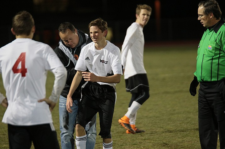 Lee Williams' coach Gabe Otero helps an injured player off the field during the final home game of the season.