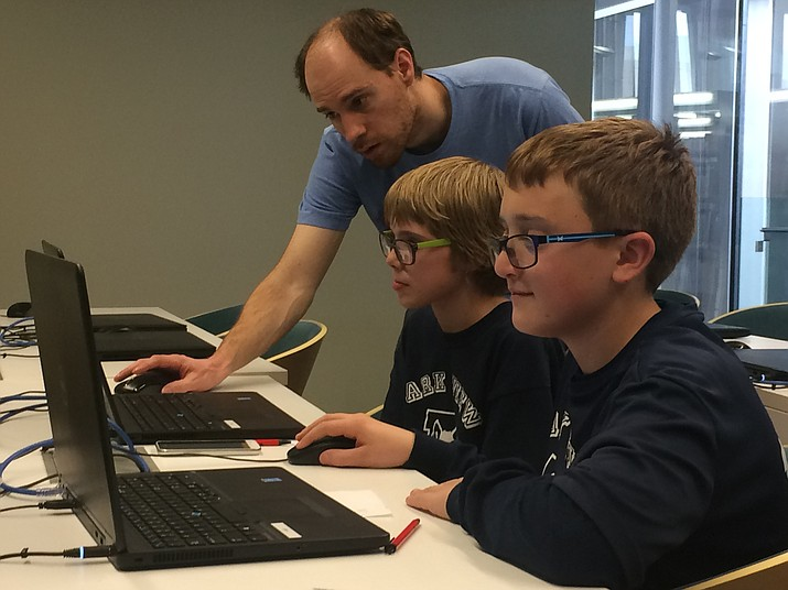 Jeff Howick helps two Kid Code Club participants with their programs.