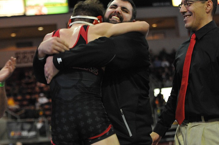 Lee Williams wrestling coach Dan Ondrejka and state champion Nic Verville embrace immediately following Verville's Division III title-winning match Friday in Prescott Valley.