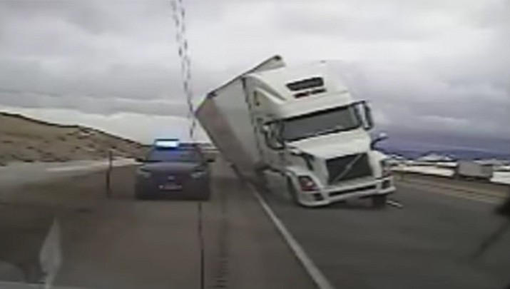 A semi truck was driving on Interstate 80 in southern Wyoming on Tuesday when it blew over onto the parked patrol car. See video below.