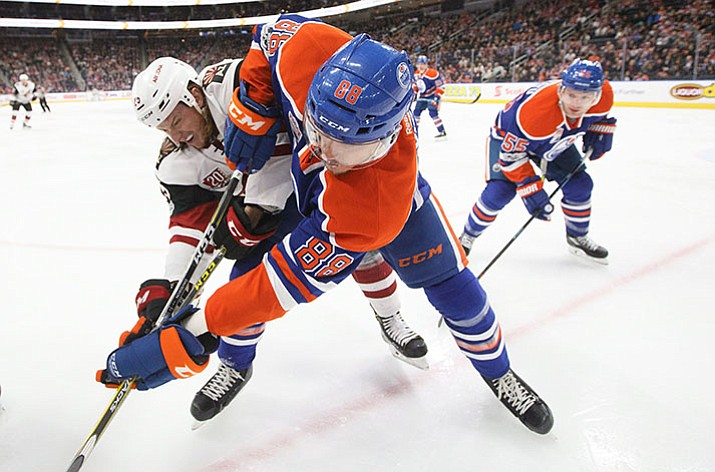 Coyotes' Ryan White and Oilers' Brandon Davidson battle for the puck Tuesday, Feb. 14.