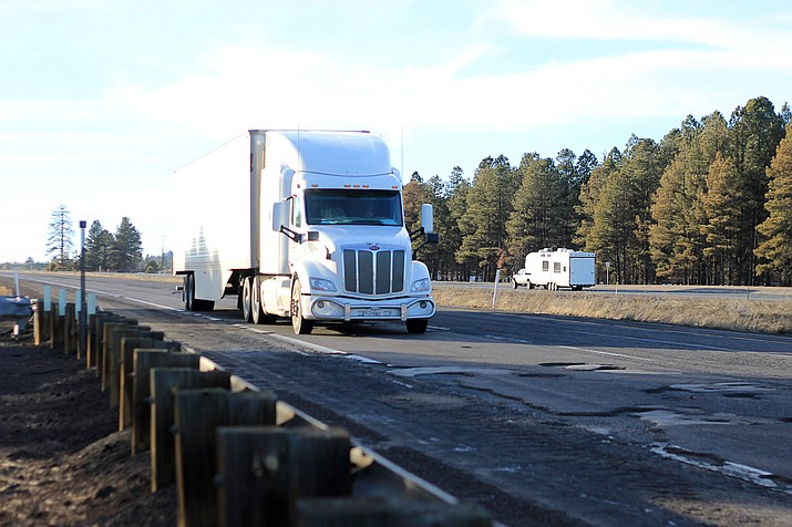 Semi-trucks stay in the left lane of Interstate 40 near Parks in an effort to dodge potholes. Numerous vehicles have been damaged by the potholes that are prevalent this winter across northern Arizona.