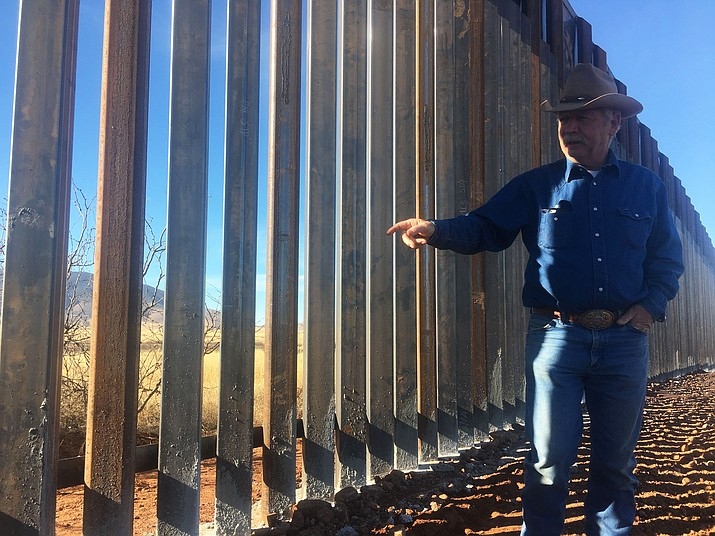 John Ladd stands near the border fence located on his ranch in Arizona. (Photo by Garrison Murphy/Cronkite News)