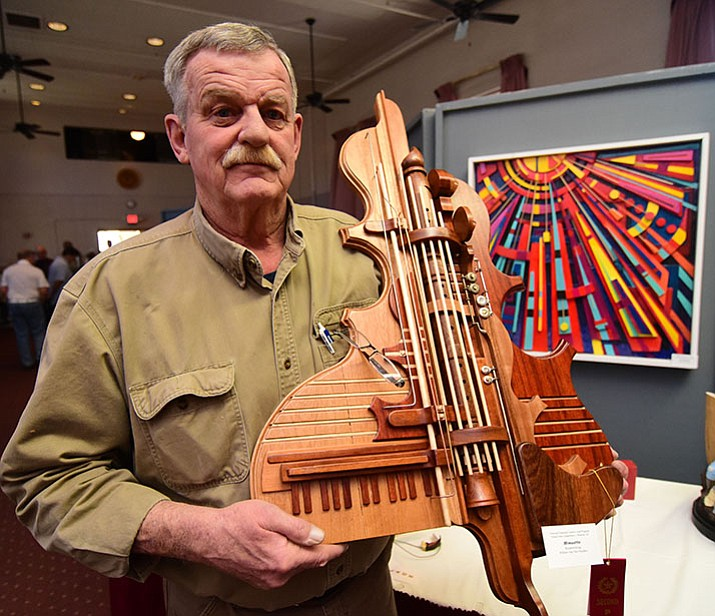 "W.B. van der Heyden holds up his woodworking piece called ""Minuette"" at the VA Creative Arts Festival in Prescott. Above is one of his musical instrument wood sculptures."