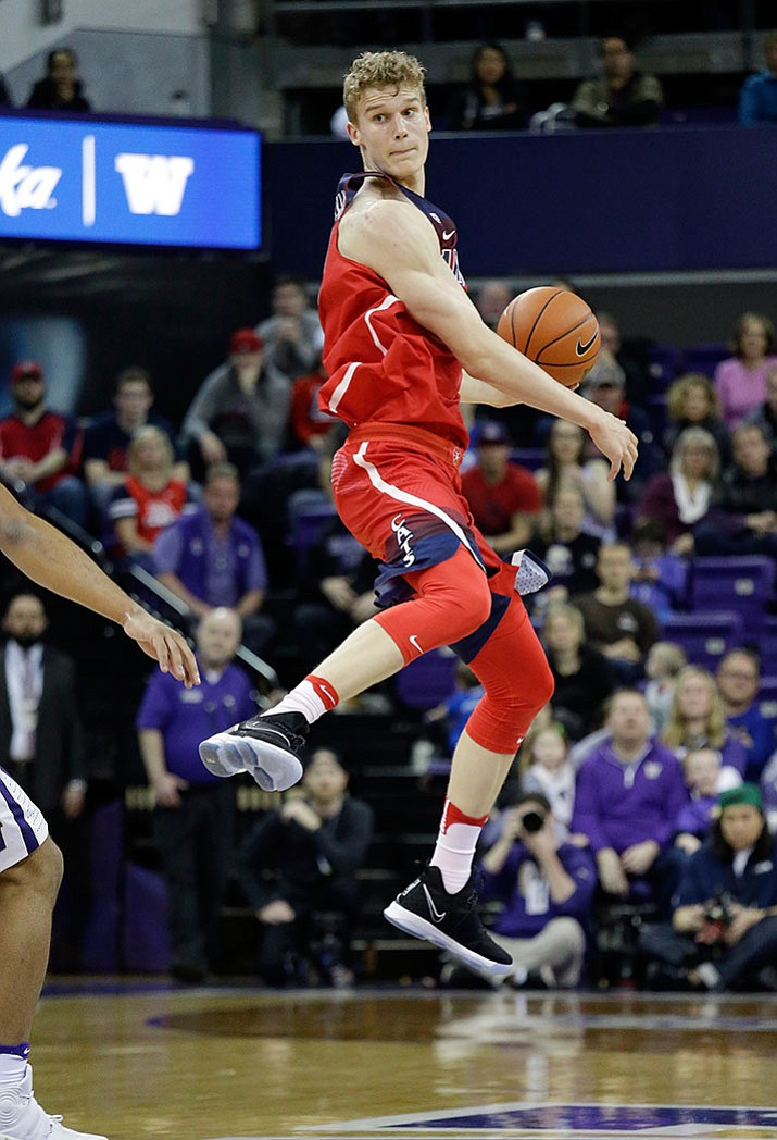 Arizona's Lauri Markkanen leaps at the half-court line to prevent a call of over and back during the first half of the team's game against Washington on Saturday, Feb. 18, in Seattle.