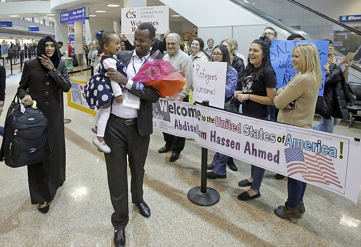 Abdisellam Hassen Ahmed, a Somali refugee who had been stuck in limbo after President Donald Trump temporarily banned refugee entries, walks with his wife Nimo Hashi, and his 2-year-old daughter, Taslim, after arriving at Salt Lake International Airport, Friday, Feb. 10, 2017, in Salt Lake City. Ahmed meet his daughter for the first time. Ahmed is among a wave of refugees around the country making belated arrivals after their trips were canceled several weeks ago after Trump's executive order.