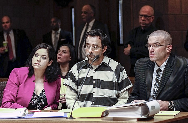 Dr. Larry Nassar, center, and his attorneys, Shannon Smith and Matt Newburg, listen to Judge Donald Allen Jr. rule that Nassar, a former Michigan State University and USA Gymnastics sports doctor, should stand trial on sexual assault charges during a hearing, Friday, Feb. 17, in Lansing, Mich. Nassar is accused of assaulting a girl from the age of 6 until the girl was 12 at his home in Holt, Mich. He's pleaded not guilty. (Robert Killips/Lansin State Journal via AP)