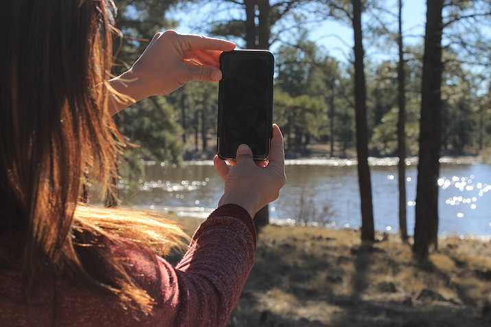 An outdoor enthusiast captures an image at Cataract Lake in Williams. The photo will be uploaded, identified and shared with researchers, scientists and nature lovers through the iNaturalist app.
