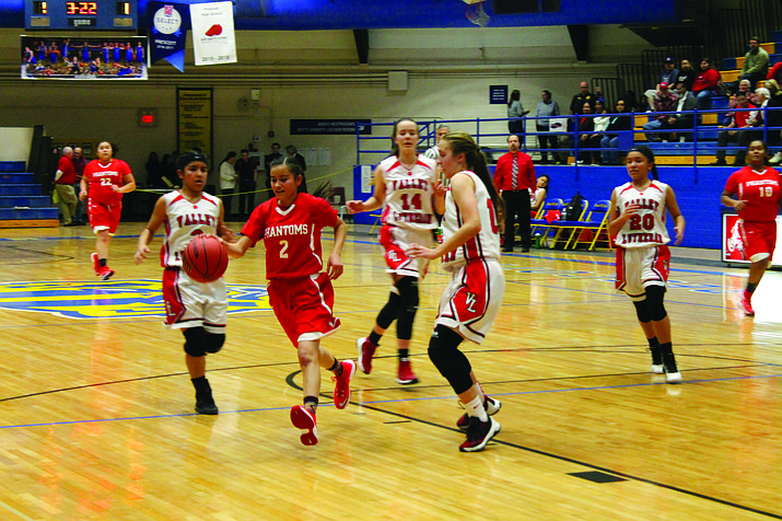Cayli Miles dribbles through three Flames defenders in the Phantoms' loss to Valley Lutheran in the state tournament Feb. 17 at Prescott High School.