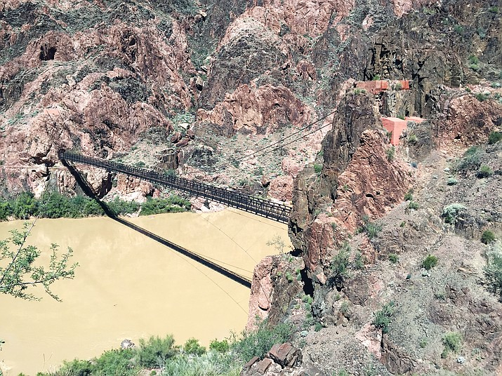 The black bridge crosses the Colorado River at the bottom of the Grand Canyon.