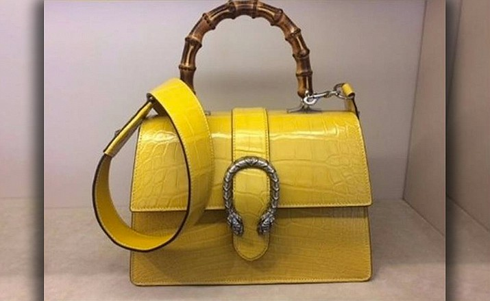 Store surveillance video shows a man walking into a Charleston, South Carolina Gucci Store on Feb. 17 carrying what looks like a cane and heading straight to a yellow crocodile skin purse with a horseshoe design and a bamboo handle.