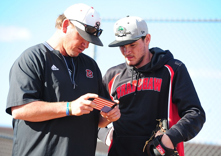 Bradshaw Mountain baseball Head Coach Brian Bundrick and pitcher Travis Robinson watch a pitching video during practice Tuesday, Feb. 14 in Prescott Valley.