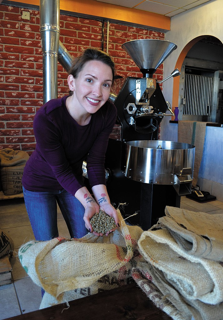 Chelsea Curry, manager of Beale St. Brews Coffee Roasting Co. shows off fresh-from the-plant coffee beans. People in Kingman like their coffee – but they might disagree on where the best cup of joe can be found.