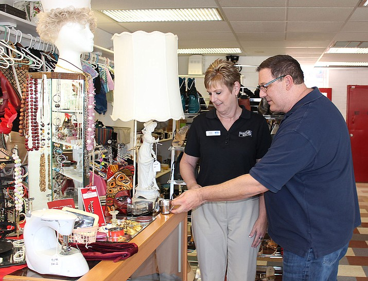 Dawn Darby, Kingman area manager for River Cities United Way, looks over some of the items for sale at Salvation Army's thrift store with Troy Palmer, director of Salvation Army.