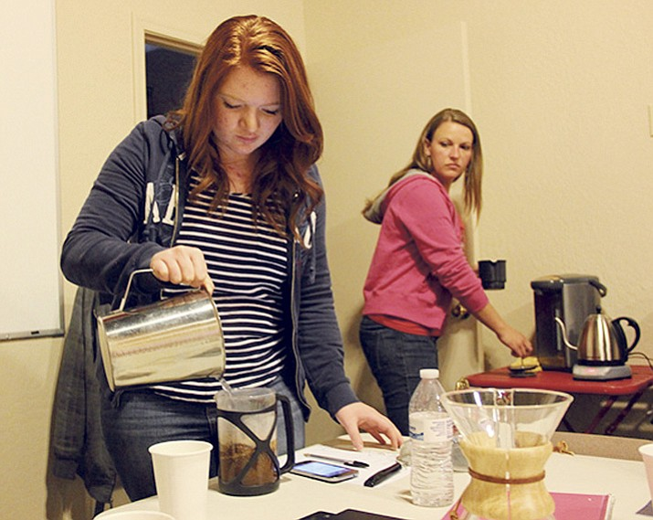 Morgan Keppel pours hot water into a French press coffee maker while her co-worker Jaimie Kaiser watches during Step One Coffee House's barista camp on Monday, Feb. 20.