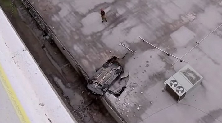 A car driven by a teenager crashed off a parking garage in Houston Sunday afternoon, falling seven stories and landing upside down onto the roof of another building.