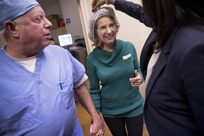 Dr. Mark Whitten, left, leads Christianne Krupinsky out of eye surgery in Washington after inserting a Raindrop inlay, a disc implanted in the cornea to reshape it for better close-up focus. This new kind of eye implant corrects presbyopia, the need for reading glasses that eventually hits all of us, usually starting in the 40s.