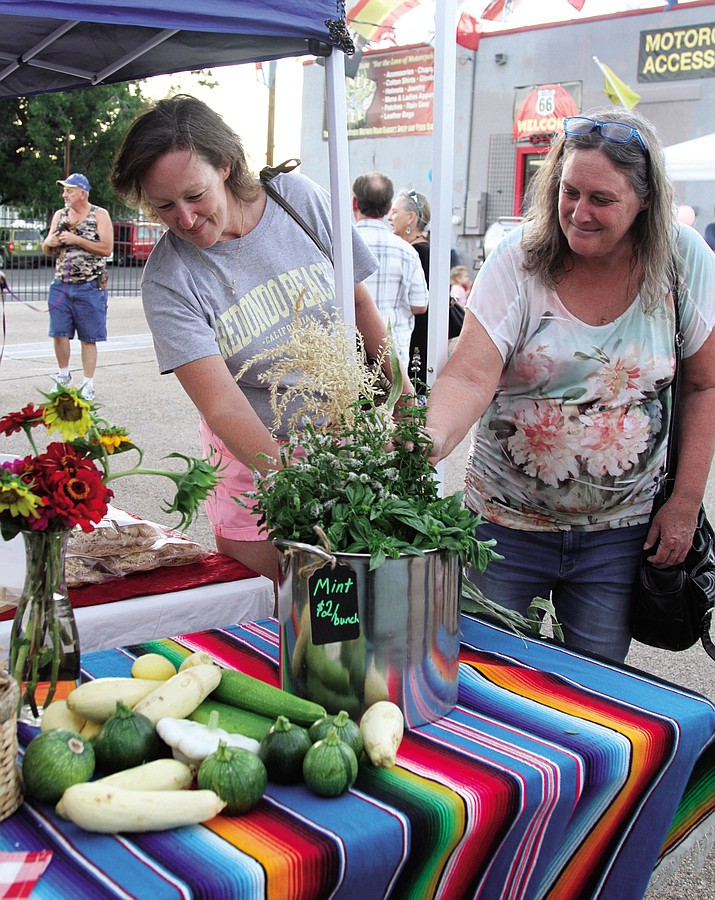Michelle (left) and Kristin Foster look at produce and herbs offered for sale by Y NOT Homestead at one of last year's markets.