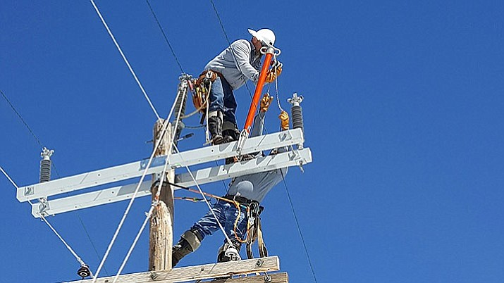 APS linemen work on restoring power to areas affected by wintry weather in late February.