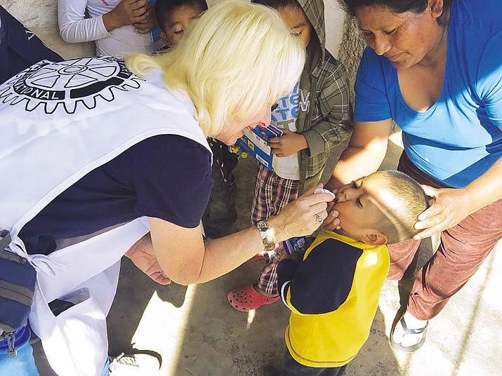 Kingman Route 66 Rotary Club member Jo Ann Oxsen treats a child near Caborca, Sonora, Mexico.