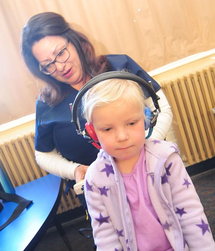 CNA Raquel Chavez checks Auria Vallejo's hearing as Yavapai County Education Service Agency nurses visited the Discovery Gardens Preschool in Prescott on March 2.