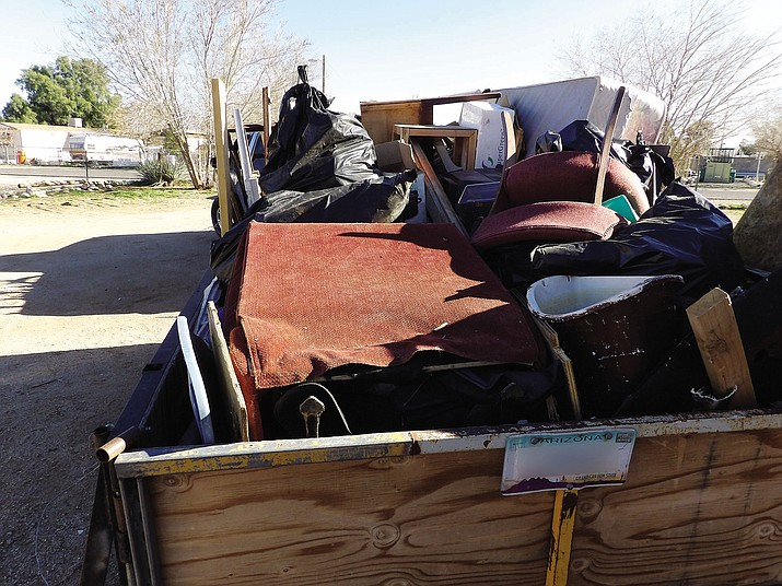 Trash removed from inside and outside of a rental home is loaded onto a trailer for a ride out to the landfill. Landlord Frank Delgado said people like him get a bad rap, but tenants who virtually destroy properties are responsible for blight.