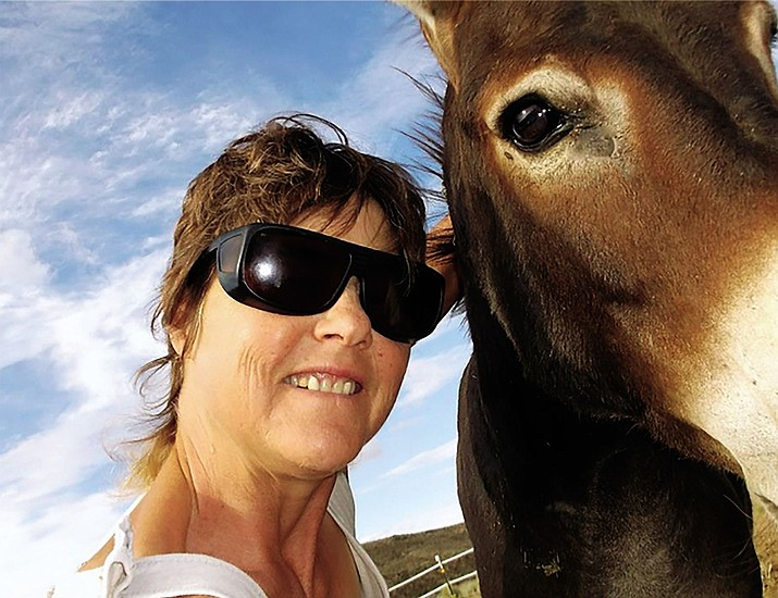 Catherine Ritlaw, shown with Poco, a wild mustang, was awarded $5,000 by Eagle Rare Kentucky Bourbon to help with expenses at Journey's End Ranch, a 30-acre animal sanctuary she founded in 2002 in Kingman.