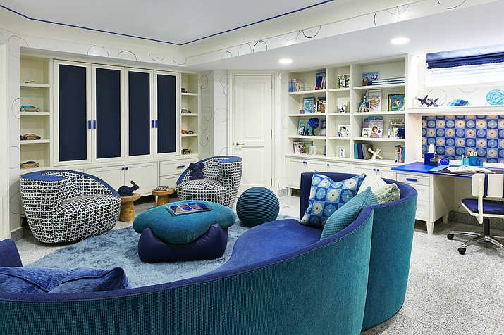 This undated photo provided by Jenny Kirschner shows a basement designed by the New York-based interior designer. Closed storage and ample shelving help keep this basement playroom feeling organized, while layered rugs and soft upholstery add plenty of warmth in this basement. (Ryan Dausch/Jenny Kirschner via AP)