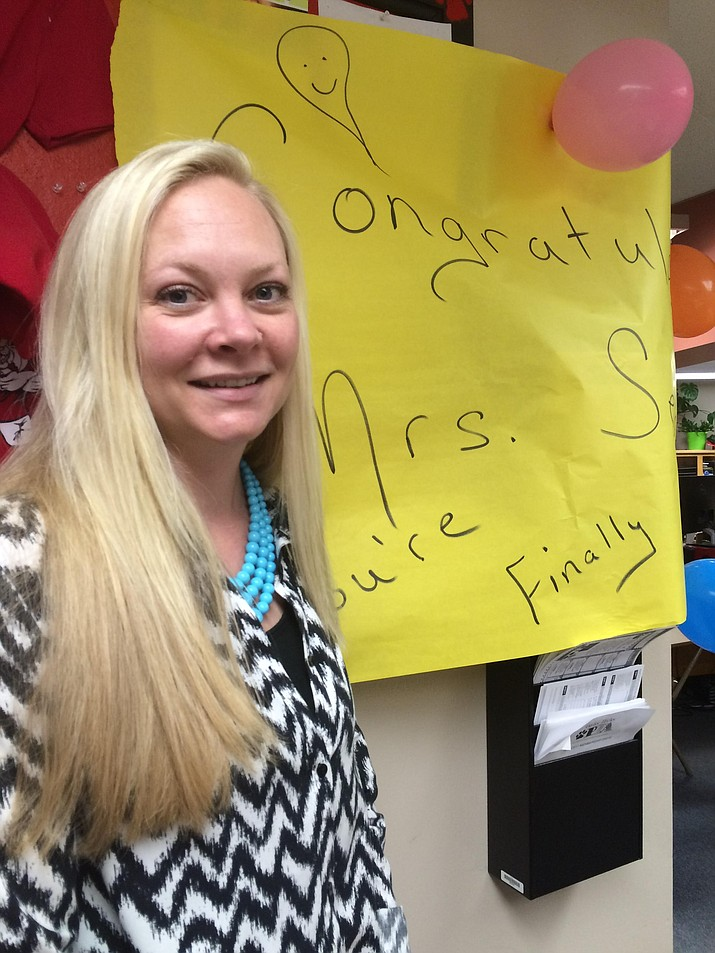 "Kelsey Secor is the new principal at Taylor Hicks Elementary. She is standing in front of the ""Congratulations – You're Finally Home"" sign."