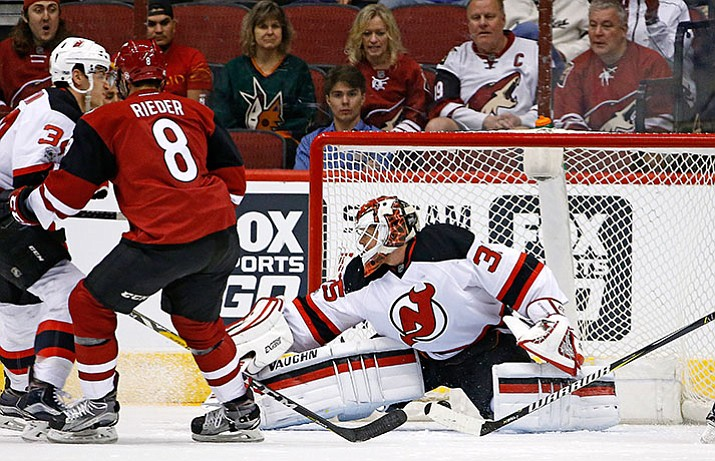 Arizona Coyotes right wing Tobias Rieder (8) scores a goal against New Jersey Devils goalie Cory Schneider, right, as Devils' Steven Santini, left, defends during the first period of an NHL hockey game Saturday, March 11, in Glendale.
