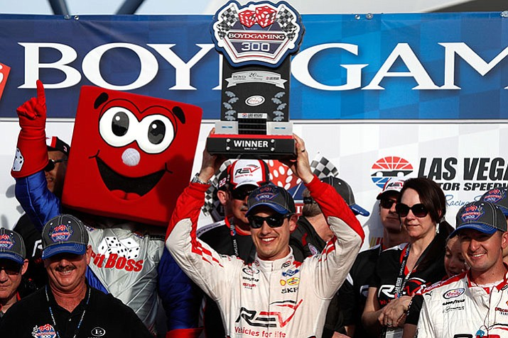 Joey Logano holds up his trophy in victory lane after winning the Boyd Gaming 300, a NASCAR Xfinity Series auto race, at the Las Vegas Motor Speedway, Saturday, March 11.