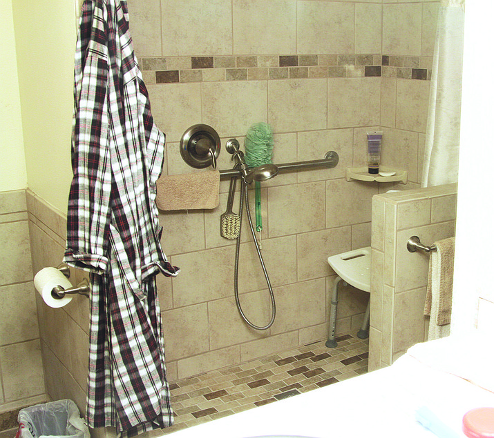 A recently renovated bathroom in Kingman built with Americans with Disabilities Act compliant handrails and toilet. The former bathtub rim was replaced with a partial shower stall to reduce risk of tripping.