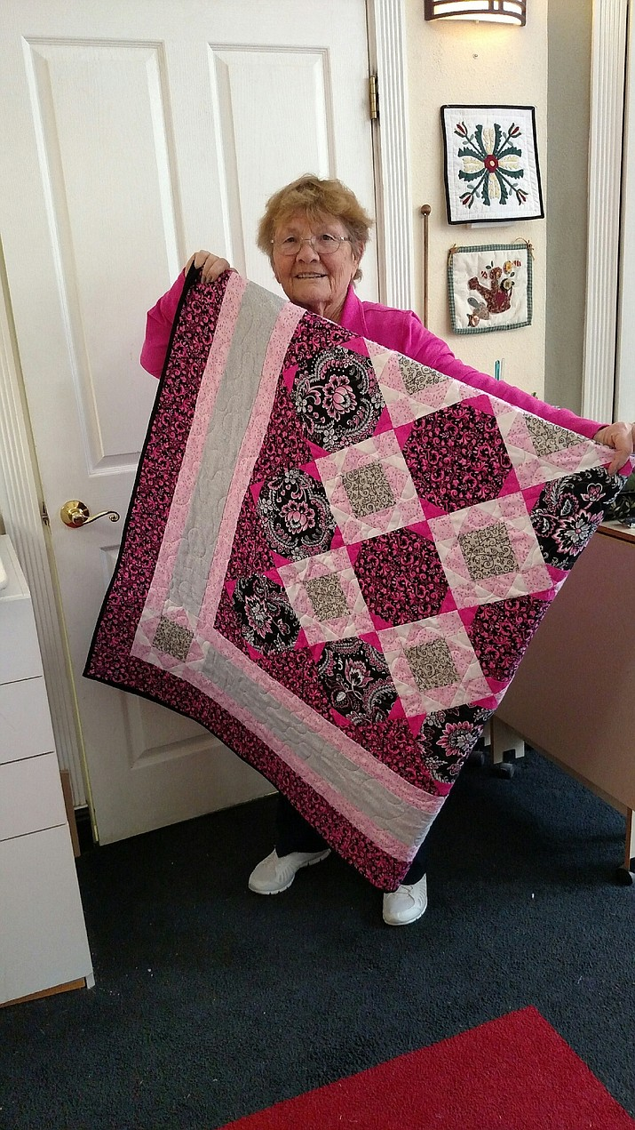 "Charlsie Ramay shows off the quilt she won as part of the ""Quilt Pink for Life"" fundraiser."