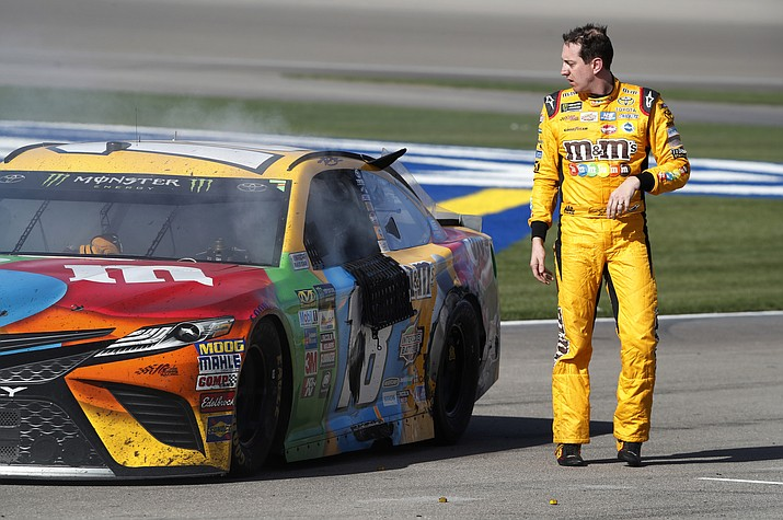 Kyle Busch walks away from his smoking car after he spun out during Sunday's NASCAR race in Las Vegas.