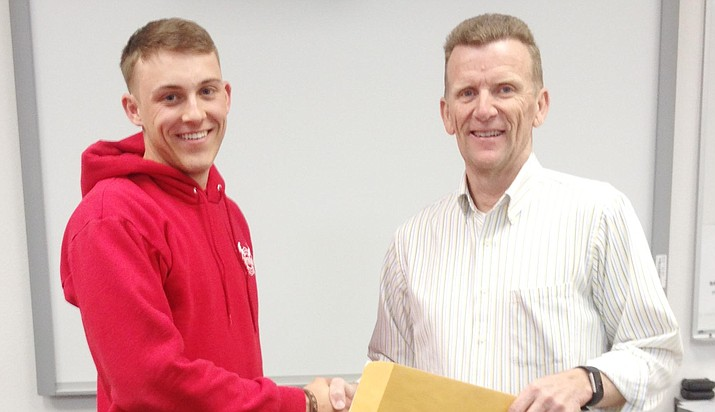 Mingus Union's Jacob Schwisow accepts first place award from Snowflake Fire Department Chief Stuart Bishop at the annual Skills USA Regional Firefighter Competition. (Courtesy photo)