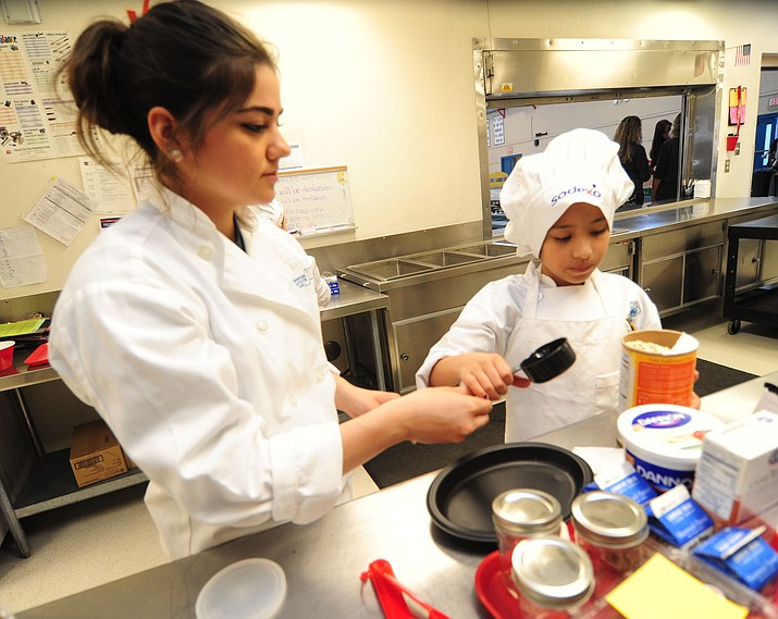 "Ava Jaime prepares her dish with Chino Valley High School mentor Rachael Pons during the finals of the ""future chef challenge"" at Del Rio Elementary School in Chino Valley Thursday, March 9.  (Les Stukenberg/The Daily Courier)"