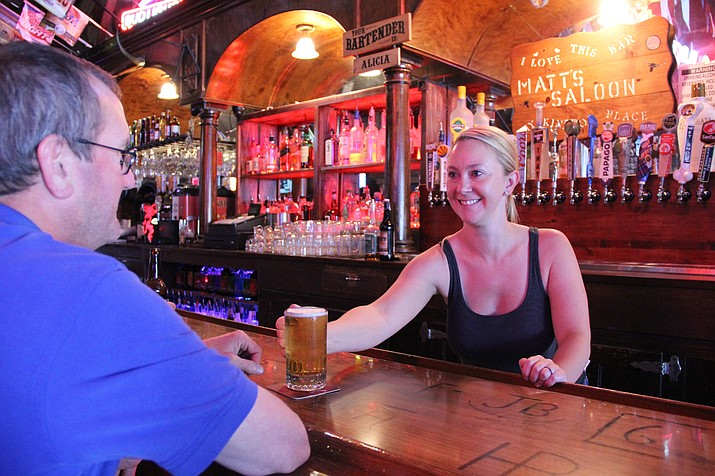 Alicia Sutton, bartender at Matt's Saloon, serves a beer to a customer.
