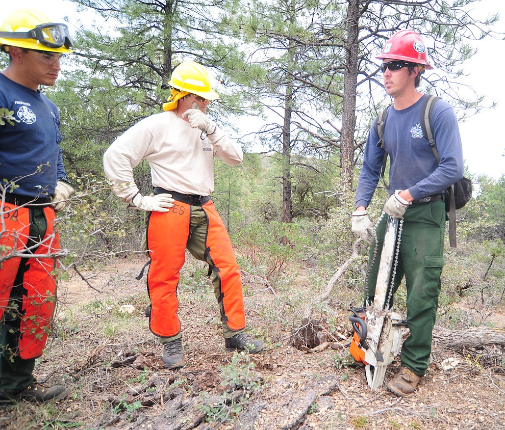 Prescott Hotshot Aaron, at right, instructs Groom Creek Fire's Logan Wallace on how to remount a thrown chain in the S212 Wildland Fire Chain Saws class during the Arizona Wildfire Academy field day Wednesday, March 15 near the Iron Spring Road and Skyline Drive area in Prescott. (Les Stukenberg/The Daily Courier)