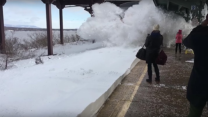 As the train arrived, it hit deep snow left by this week's major East Coast storm. The impact sent a huge wave of snow flying across the platform, engulfing people close to the tracks. See video below.