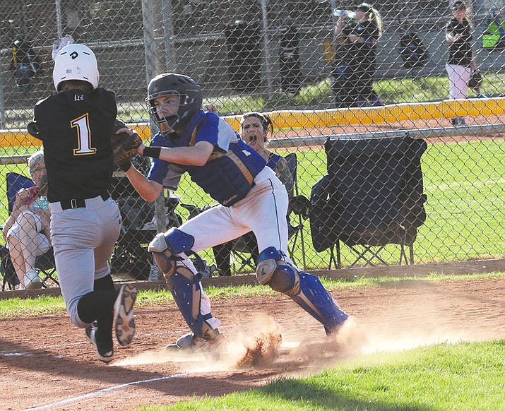 Kingman Academy catcher Bradley Hecker blocks the plate to prevent Lake Havasu's Taylor Dreisbach from scoring Wednesday afternoon.