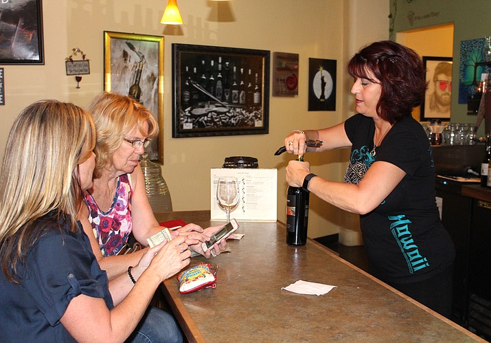 Diana Caldon opens a bottle of wine for customers at Diana's Cellar Door in downtown Kingman. She definitely thinks the nation is divided politically and socially, judging from conversation she hears at the wine bar.