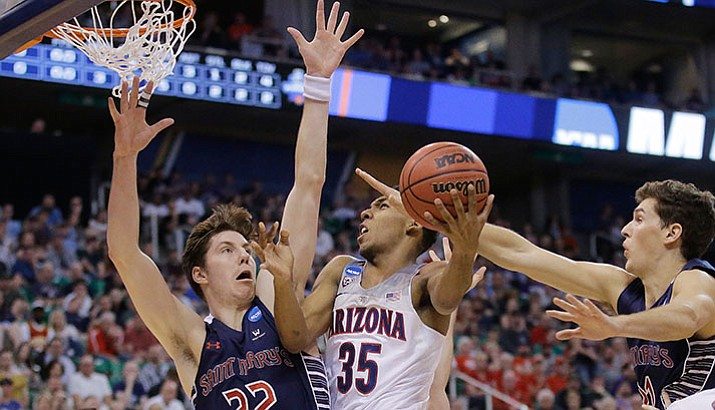 Arizona guard Allonzo Trier goes to the basket as Saint Mary's Dane Pineau (22) and Evan Fitzner, right, defend during their second-round college basketball game in the men's NCAA Tournament, Saturday, March 18, in Salt Lake City.