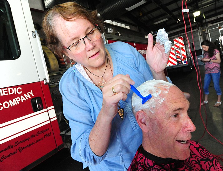 Patty Brookins shaves the head of Capt. Brian Burch as Central Arizona Fire & Medical firefighters shave their heads to support their Human Resources Manager Brookins Saturday, March 18 in Prescott Valley.
