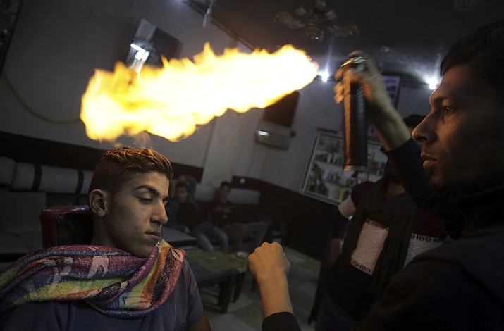 """Palestinian hair dresser Ramadan Adwan uses fire to straighten the hair of a costumer in his barber shop in the Rafah refugee camp in the Gaza Strip. After cutting and combing, the barber applies what he calls """"special"""" lotion and powder to client's heads to protect their skin before using an aerosol can to burn hair off."""