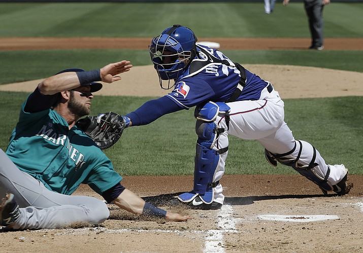 Texas Rangers catcher A.J. Jimenez tags out Seattle Mariners' Mitch Haniger during the first inning of a spring training baseball game Sunday, March 19, in Surprise.