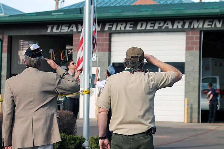 Scout leader Michael Hoblin and American Legion Cordova Post 13 officer Rodger Ely salute a new flag as it is raised over the Tusayan Fire Department.