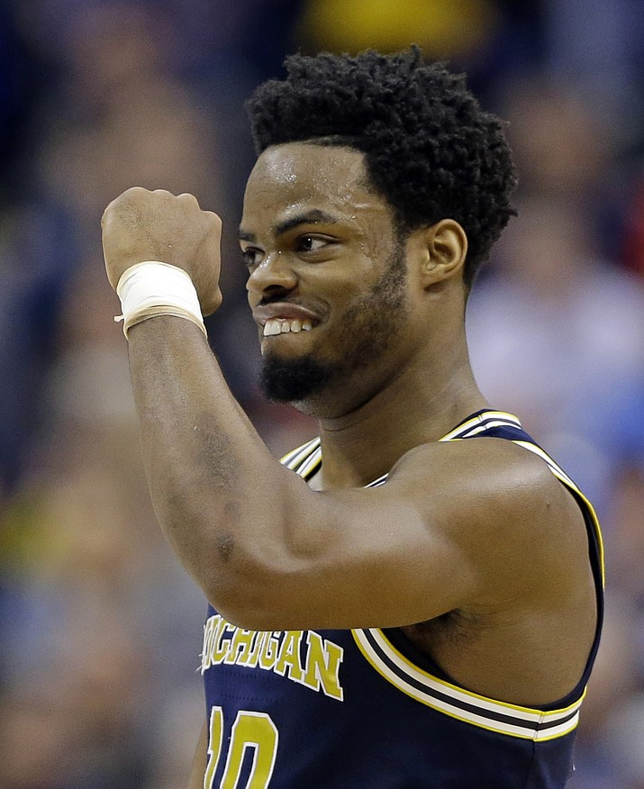 Michigan guard Derrick Walton Jr. (10) celebrates a 73-69 win over Louisville in a second-round game in the men's NCAA college basketball tournament in Indianapolis on March 19. (Michael Conroy/AP)