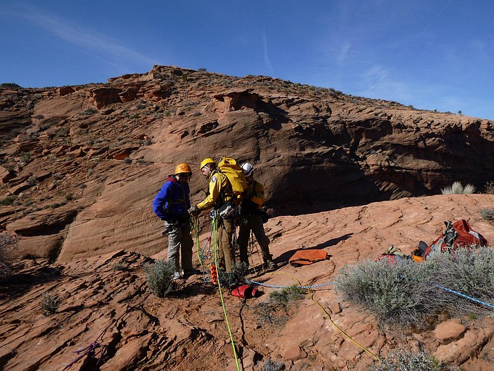 Coconino County search and rescue team members help two hikers stranded below the rim of Waterholes Canyon near Page.