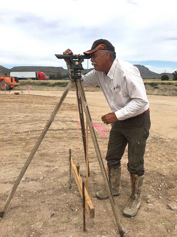 Wade Eckel uses surveying equipment to get a straight line for plumbing pipes that will be going into the Home 2 Suites extended-stay hotel by Hilton being built in Kingman. The week of March 19-25 is declared National Surveyors Week by a 1984 proclamation of President Ronald Reagan.